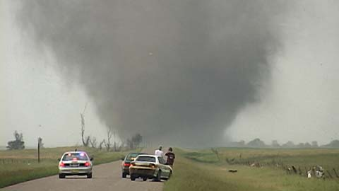 People stopped on rural road observing twister in distance
